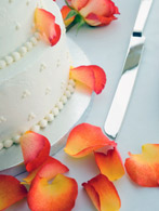 Beautiful cake with orange rose peddals scattered about