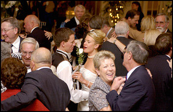 Main image of married couple on dancefloor surrounded by guests.